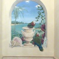 The birds are rare Bahama Parrots, the shell and tile products of local ceramic artisans. The urn matches the marble tiles of the room.